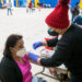 LA County Department of Health Services Medical Service Coordinator Lucy Felix administers a COVID-19 vaccination to Consuelo Lee at the Balboa Sports Complex in Encino, Jan. 26, 2021. (Photo/Michael Owen Baker)